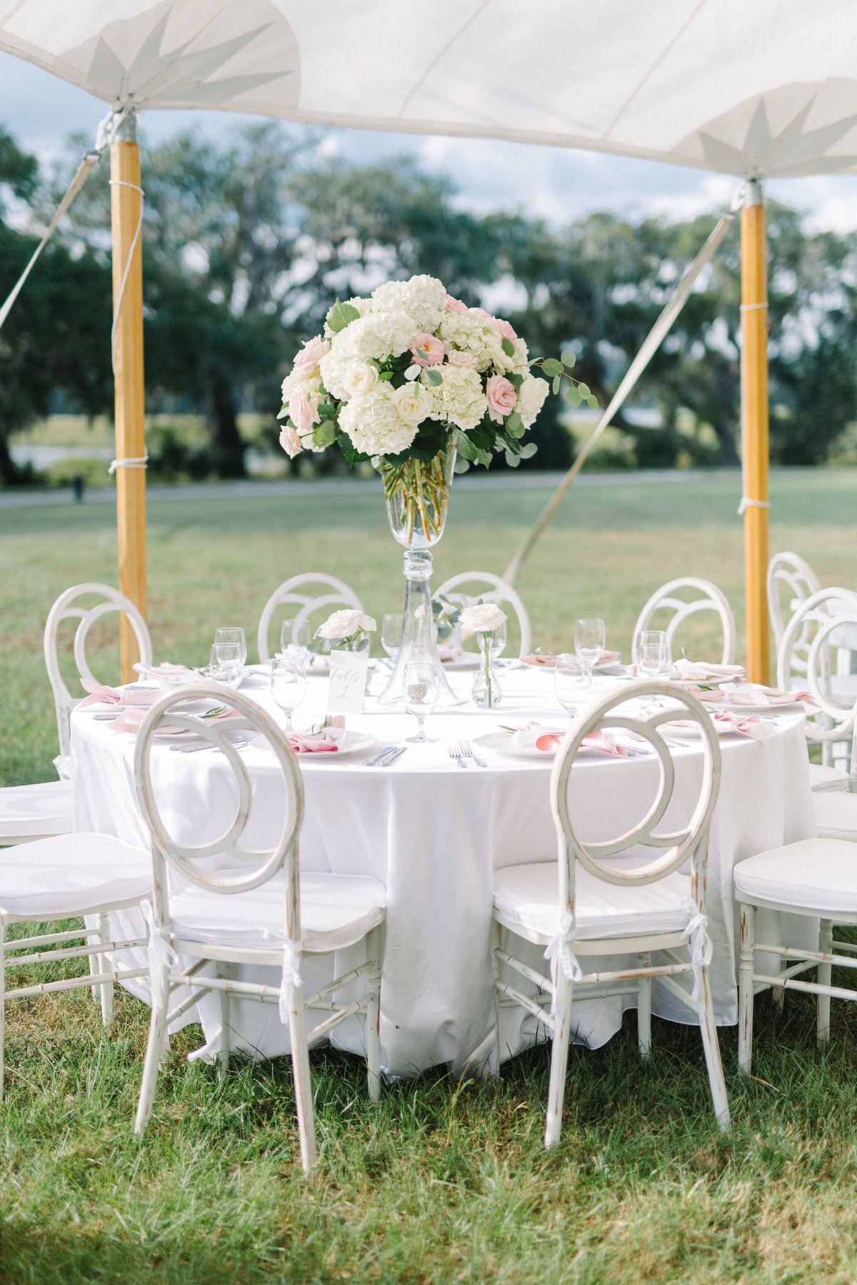 White and Blush Wedding Reception with Tall Hydrangea Centerpiece and White Chloe Chairs  under Sailcloth Tent at Boone Hall