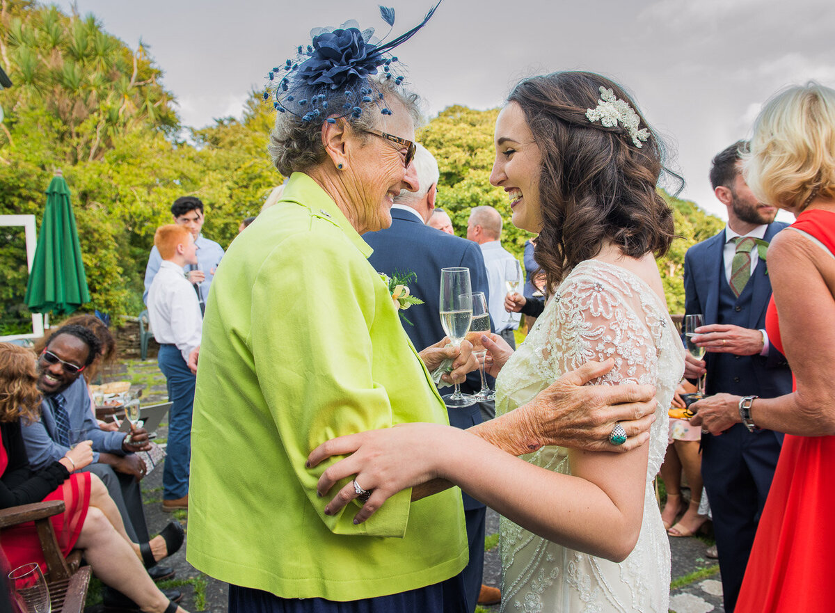 grandmother in lime green jacket and navy fascinator embracing her grand daughter wearing a vintage, beaded wedding dress in Kerry