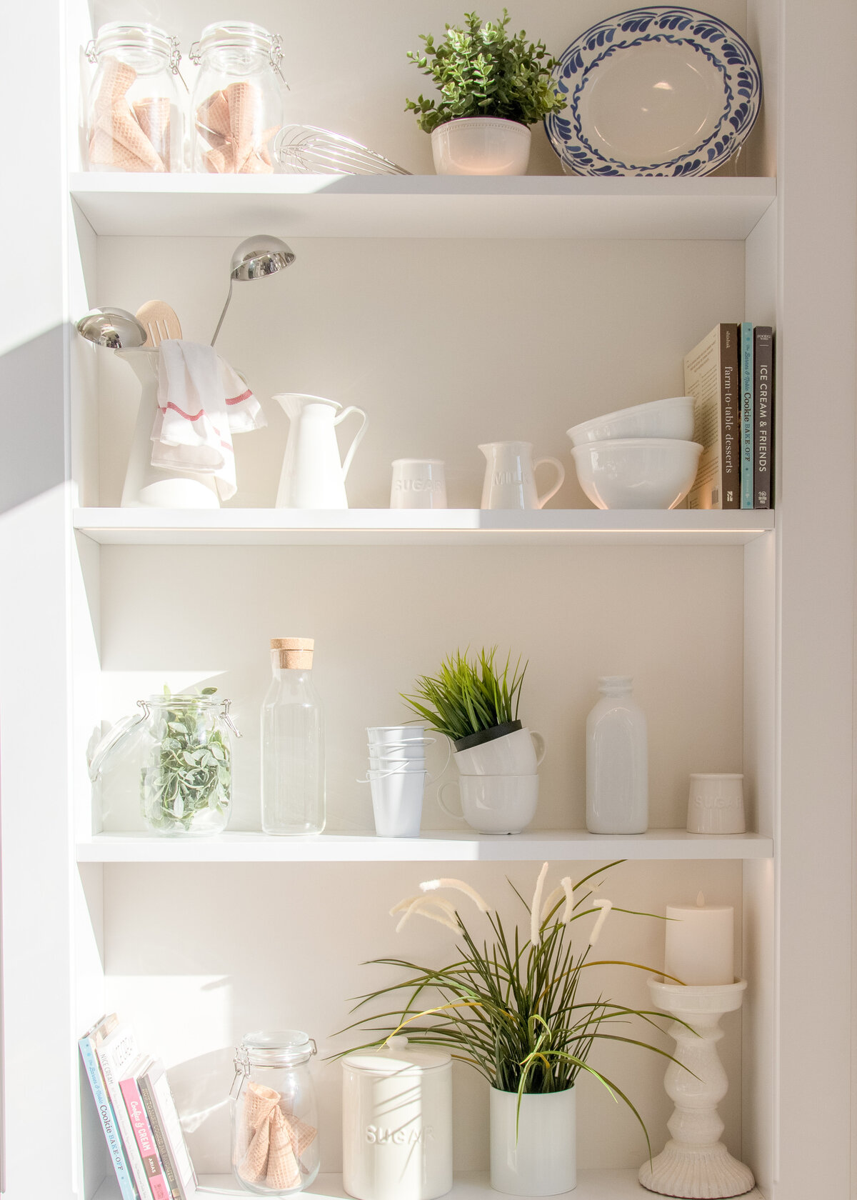 A white pantry is decorated with plates and bowls alongside herbs and a glass bottle.