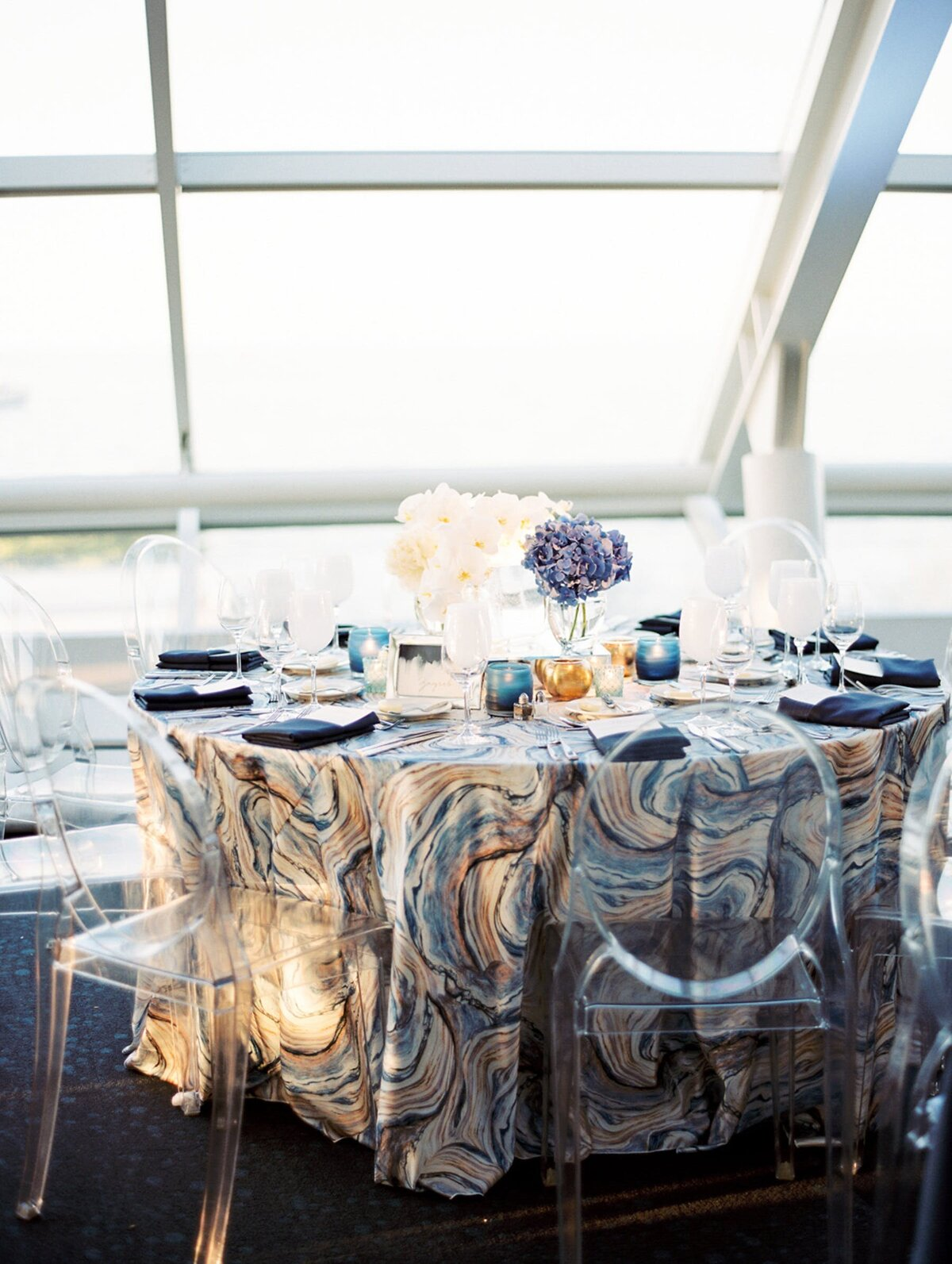 Reception table with blue, white, and gold table linen