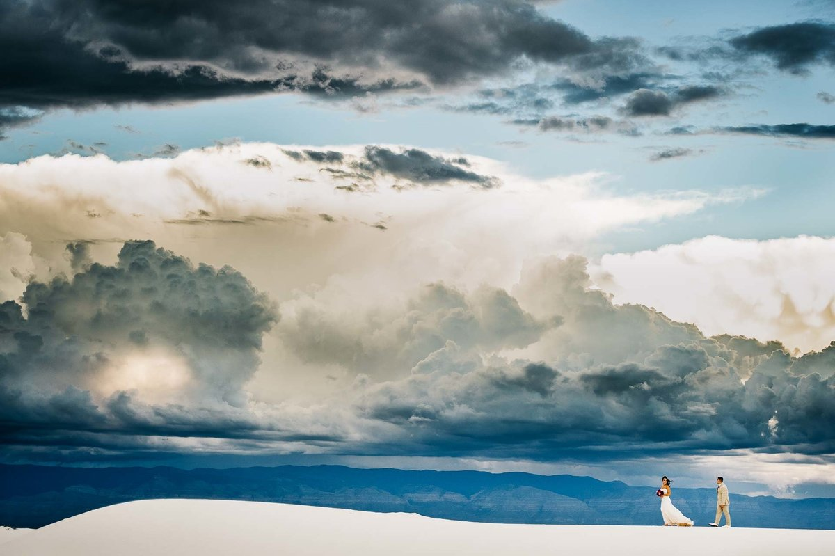 bride and groom walking on dunes at white sands national park in el paso texas by stephane lemaire photography