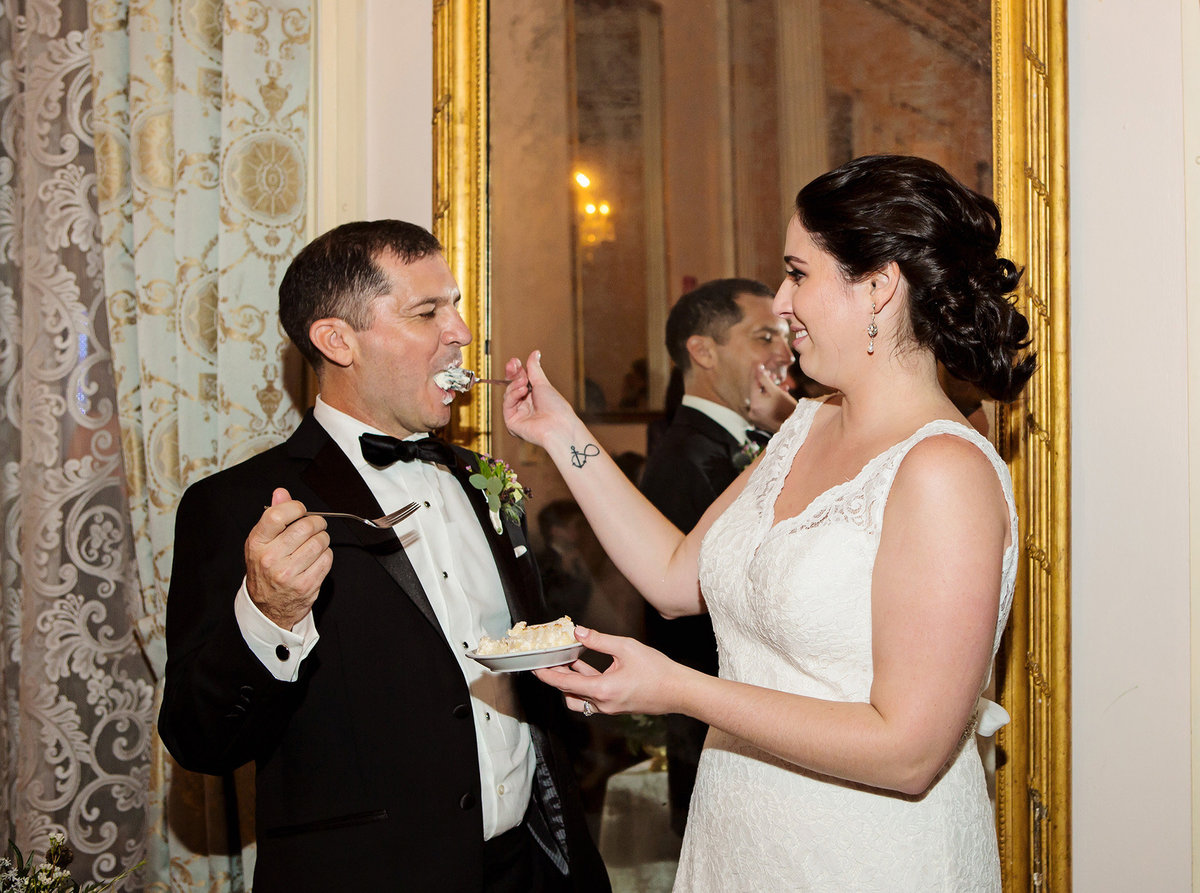 new orleans bride feeds her groom wedding cake at The Columns Hotel