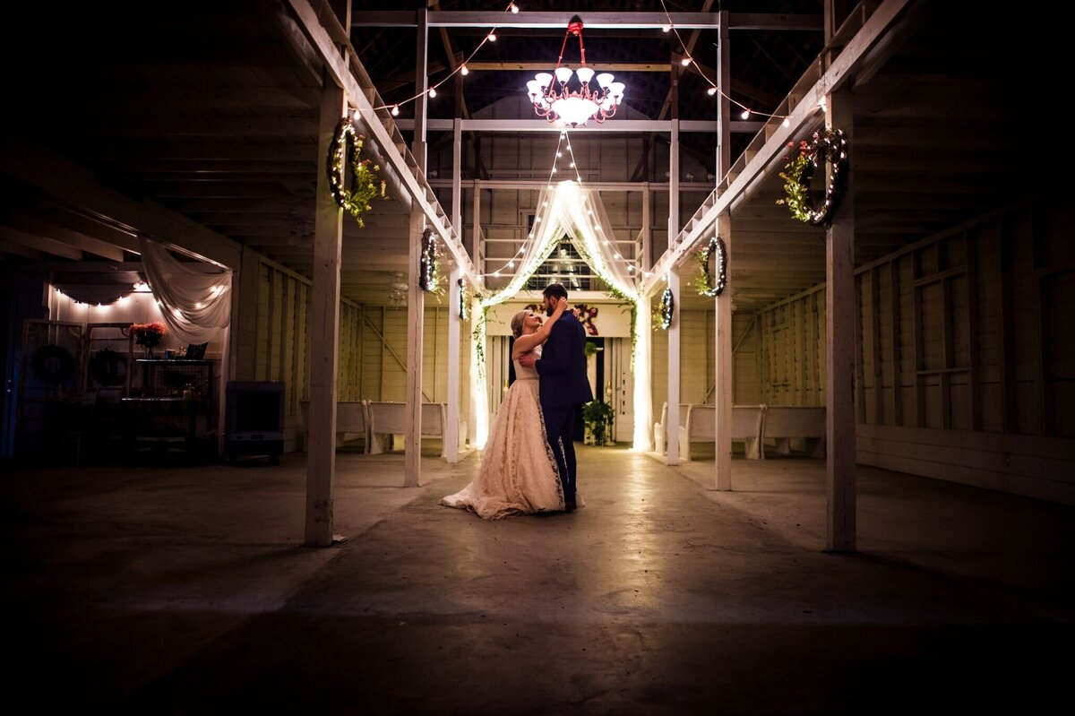 A bride and groom's last dance of the night in a dimly lit reception hall with ambient lighting