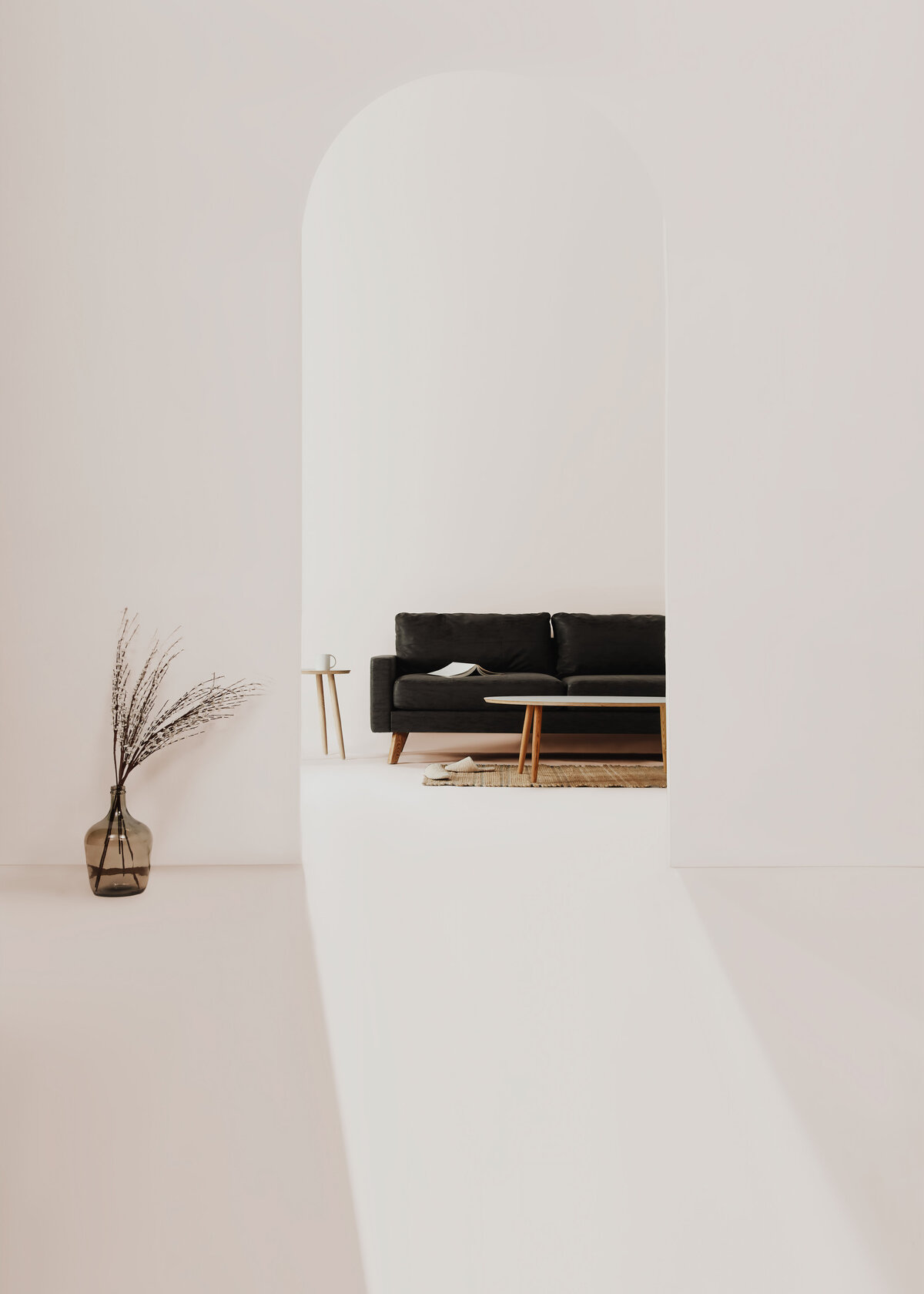 A charcoal grey sofa is in the background of a minimal white room with a sleek archway entrance.