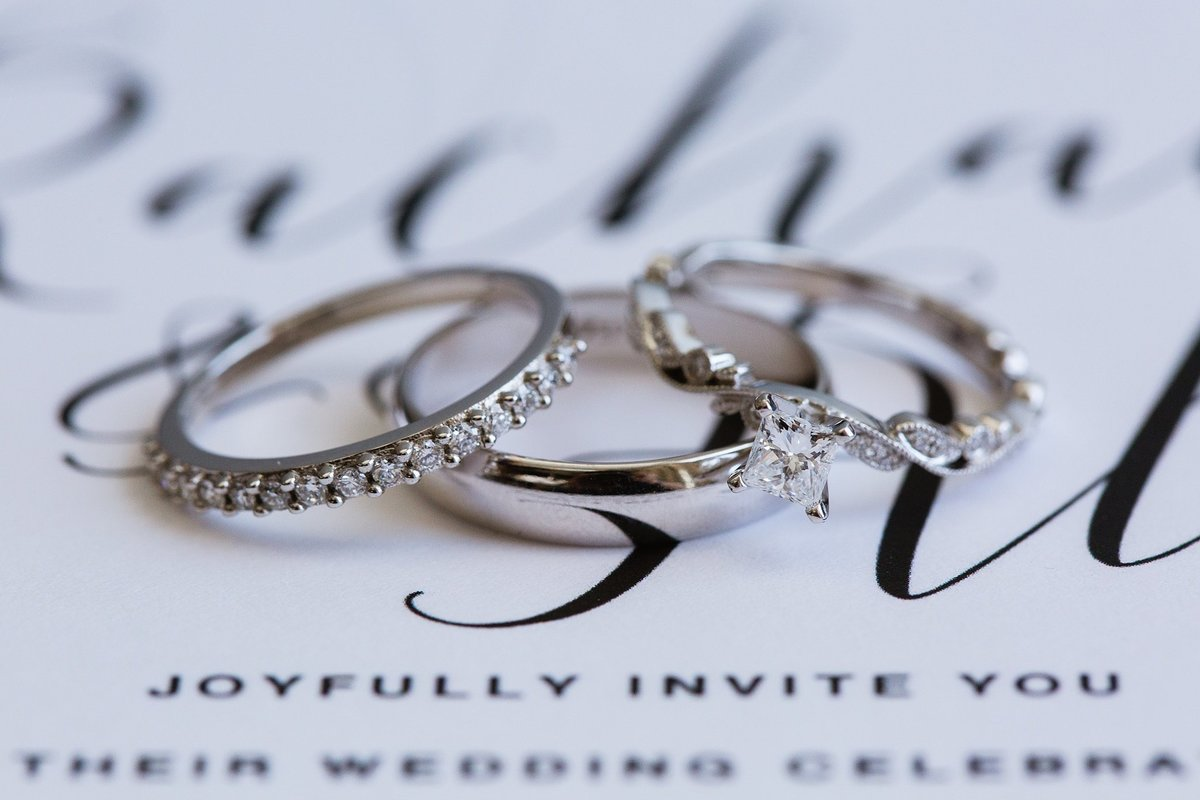 Wedding rings on script invitation by Phoenix wedding photographer PMA Photography.