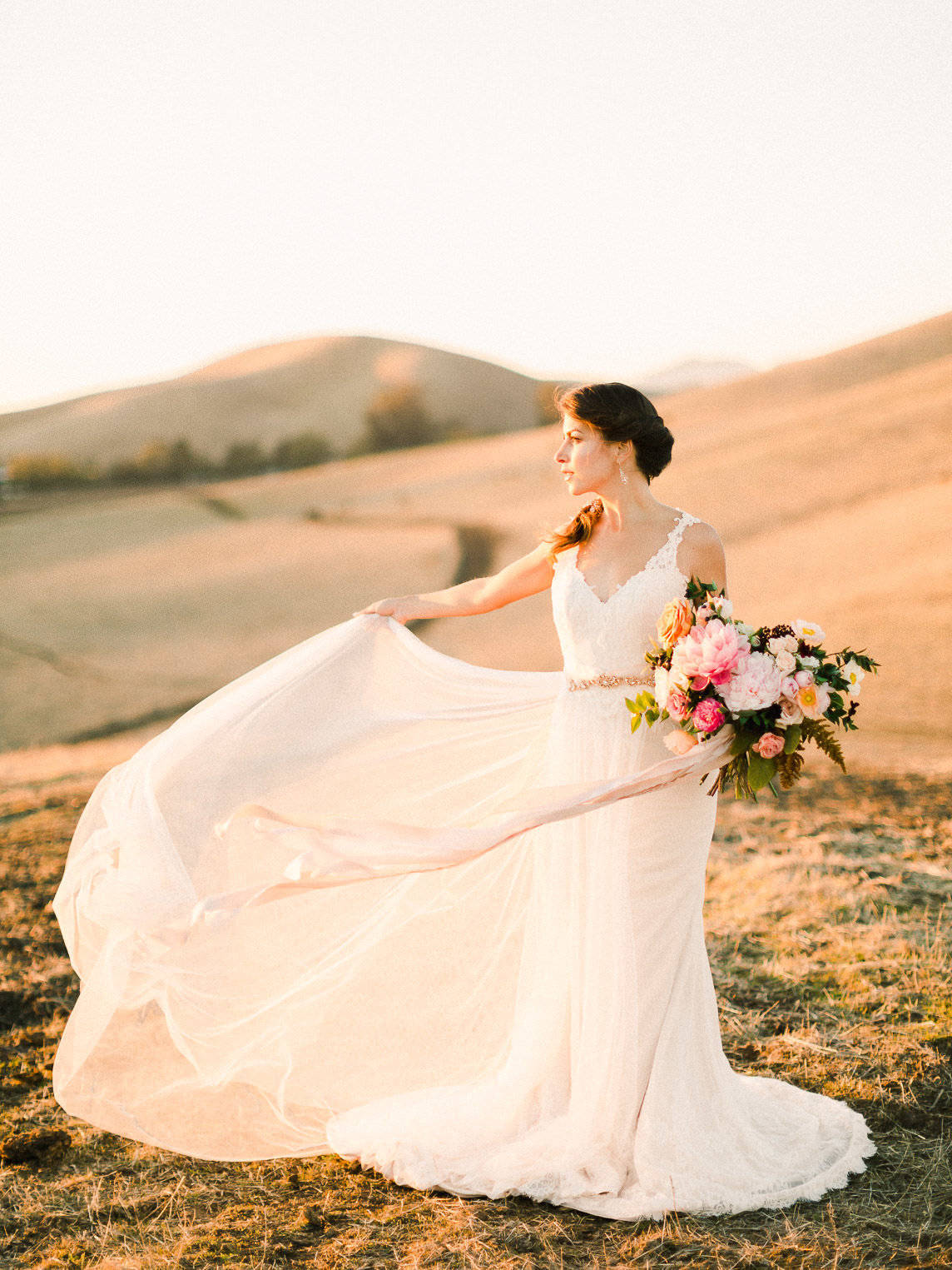 Bride in wedding dress holding bouquet on hill at sunset with skirt whipping in wind