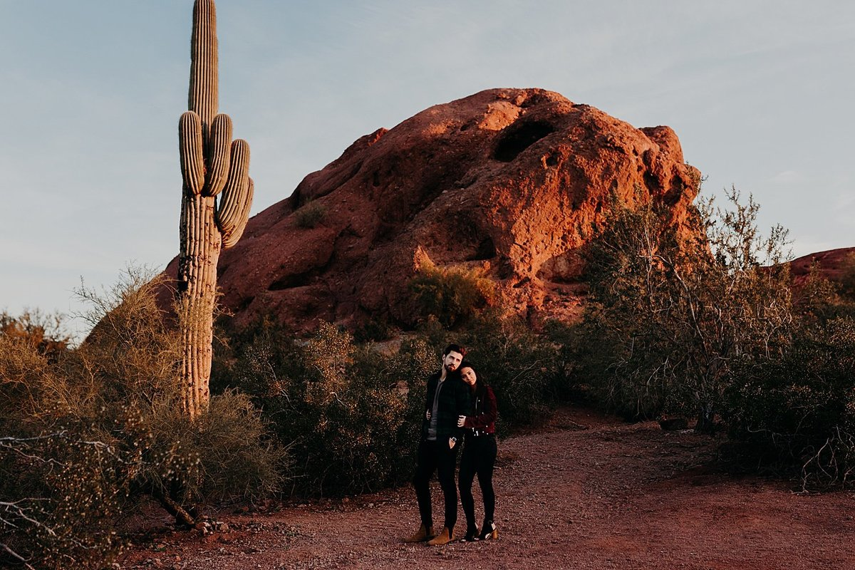 Wife hugs husband from behind while standing near tall saguaro in Papago Park