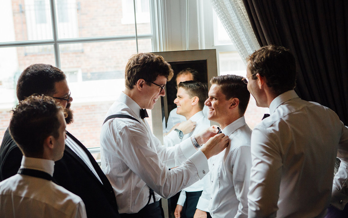 Best man adjusting grooms tie