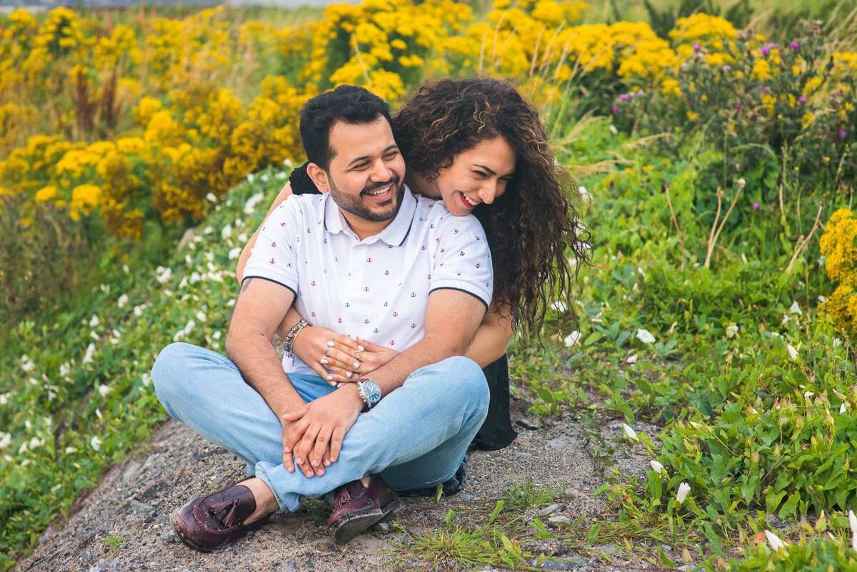 asian couple sitting on a rock laughing and surrounded by yellow flowers