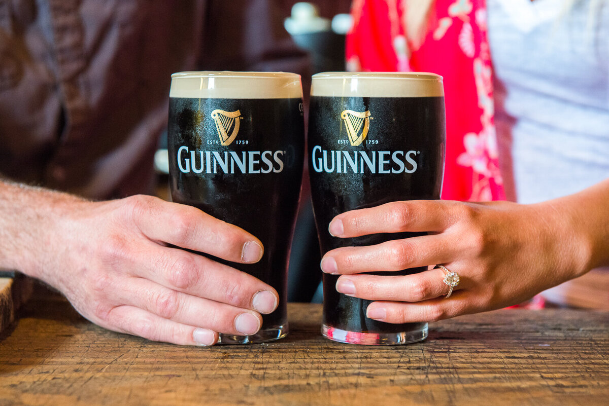 Close-up of a couples hands with engagement ring holding onto pints of Guinness