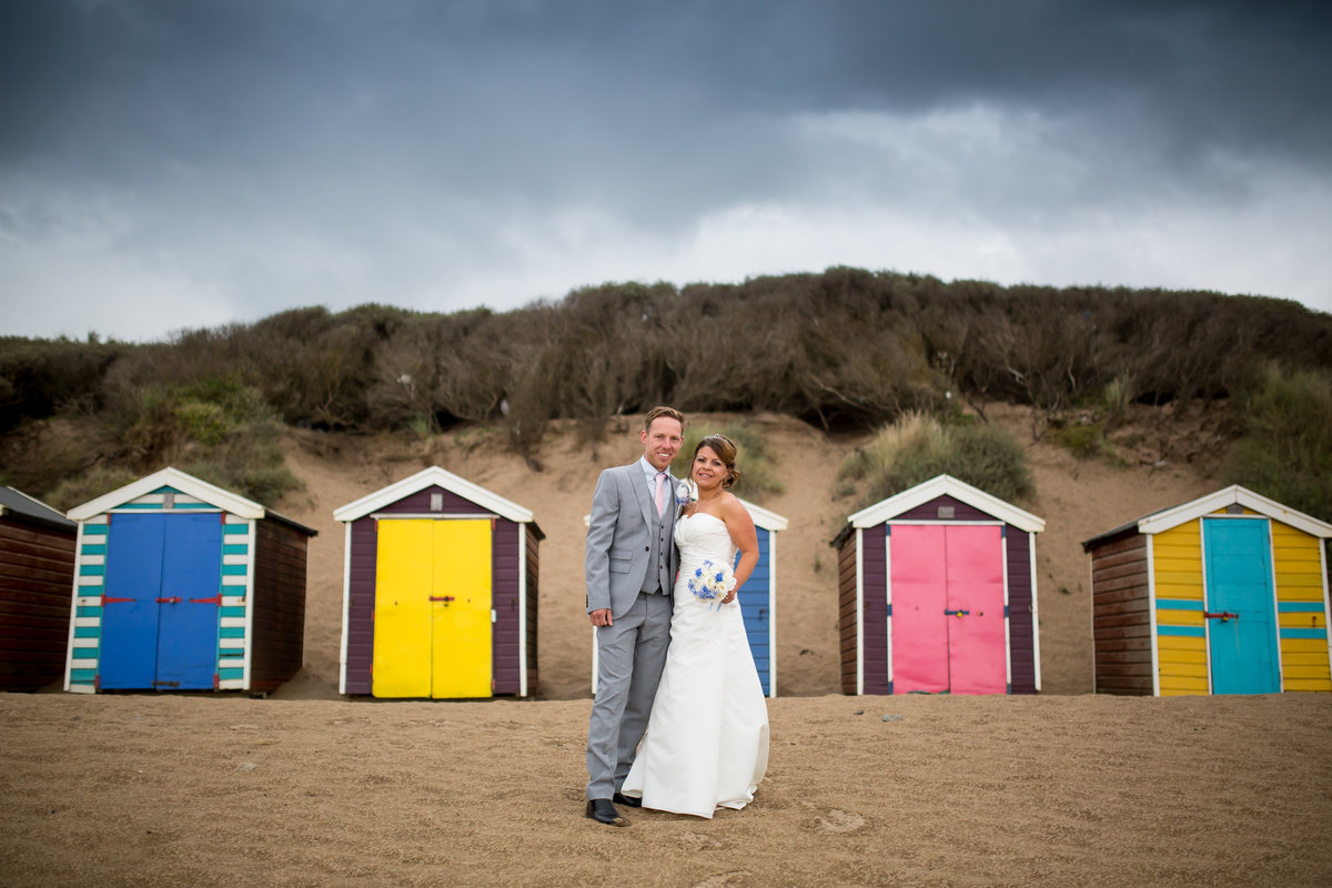 wedding photo of couple in front of beach huts in woolacombe bay devon