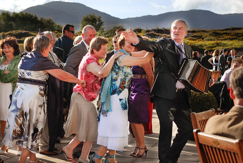 guests doing a dance train on the terrace of the Sneem Hotel while a man plays an accordian