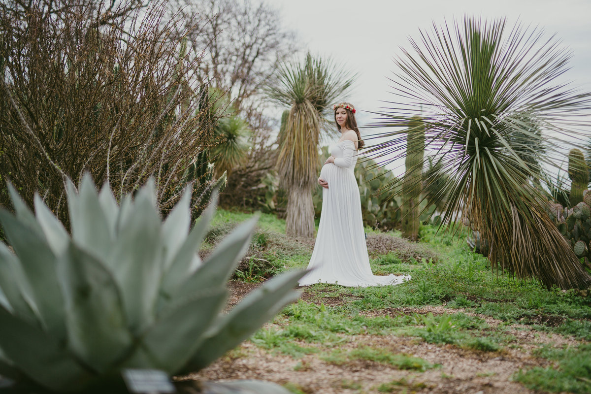 woman in boho maternity dress surrounded by succulents for her San Antonio maternity photography session at Botanical Garden