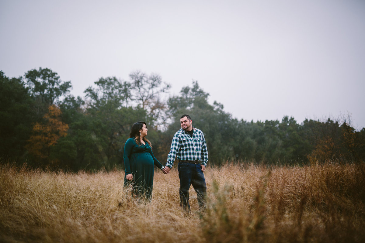 Pregnant couple holding hands in a grassy field for their maternity photography session in San Antonio.
