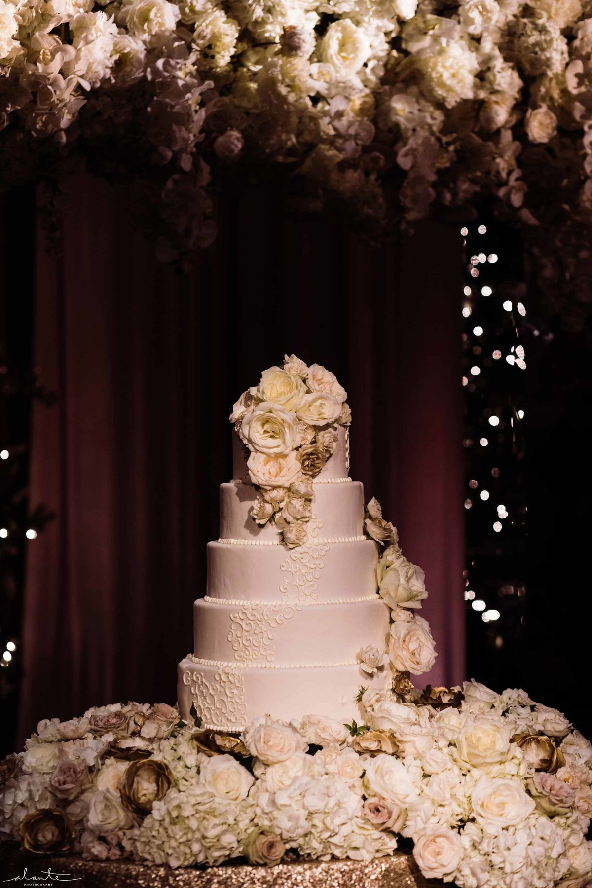 White tired wedding cake surrounded by white flowers.