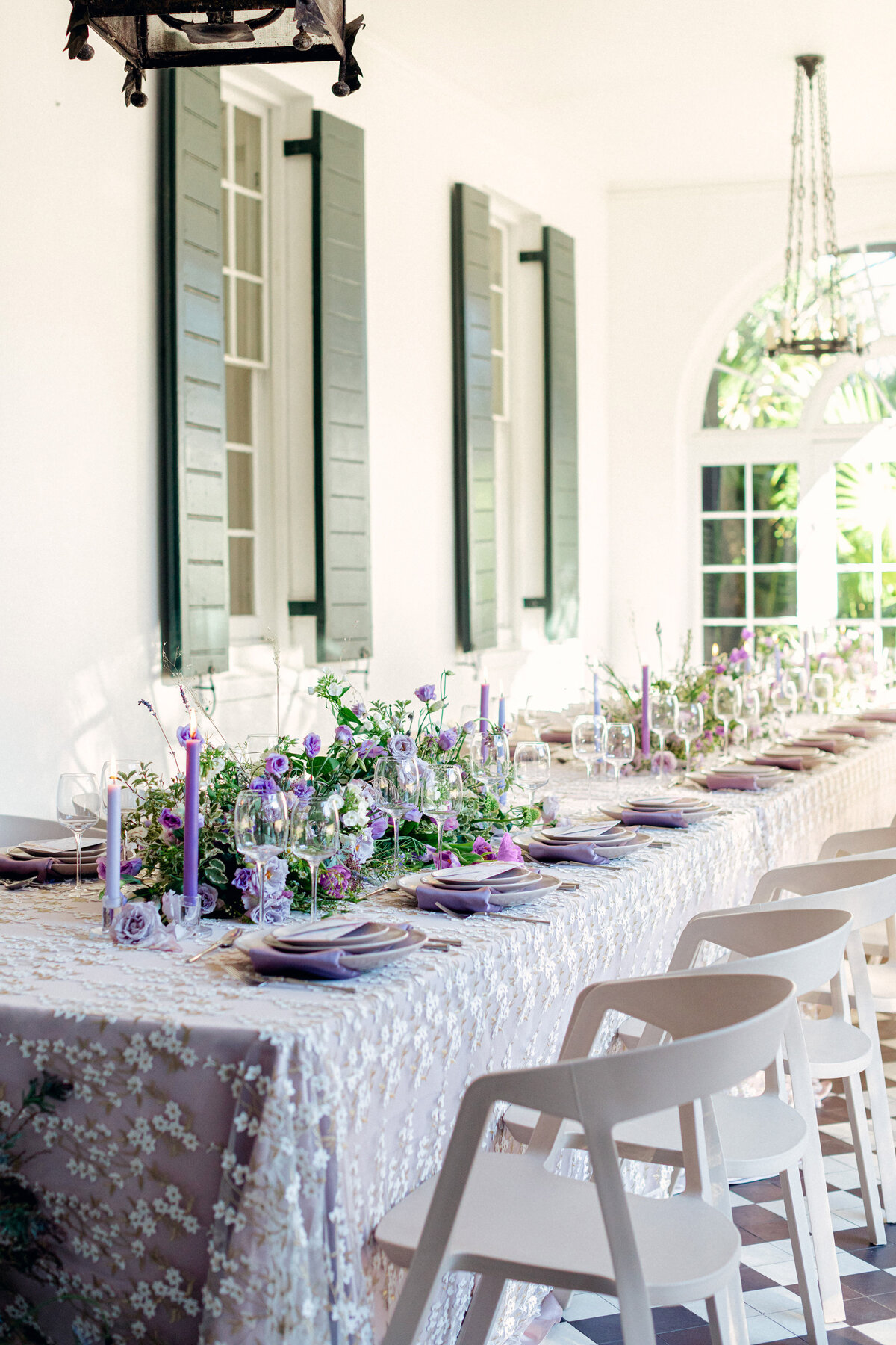 Reception table with purple florals in patio room at Lowndes Grove Charleston Wedding