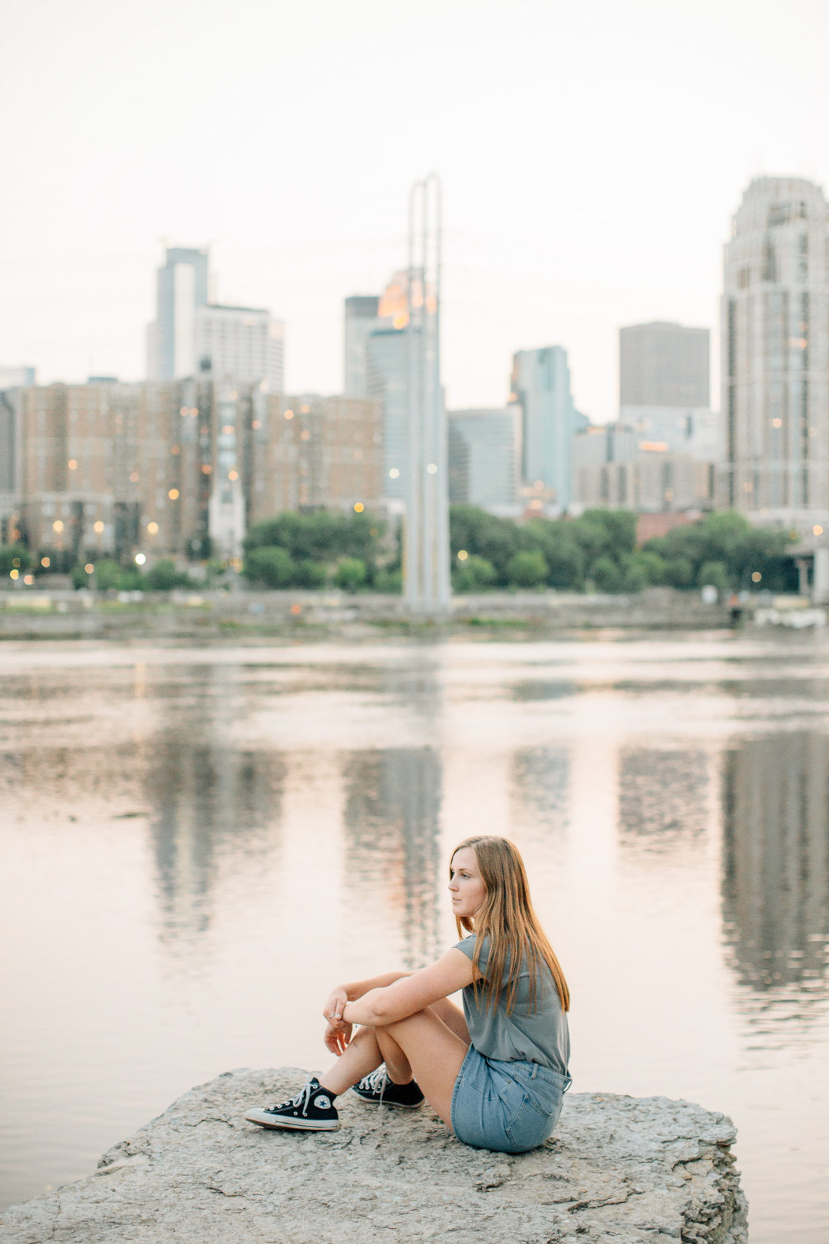 senior girl sits on post in front of minneapolis city skyline over the river