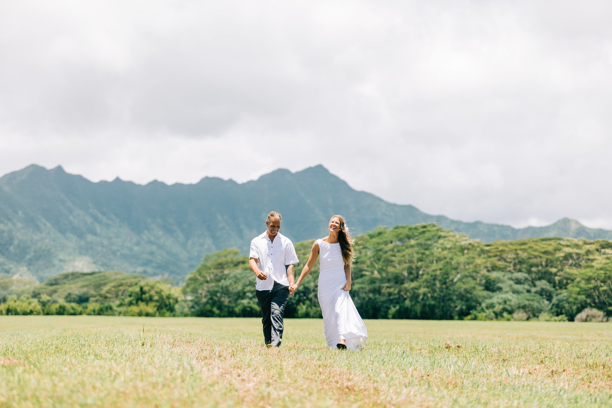 smiling wedding couple walking in a open field with mountains in background