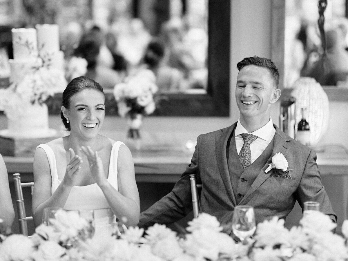 Bride and groom sitting at table laughing and clapping at speeches