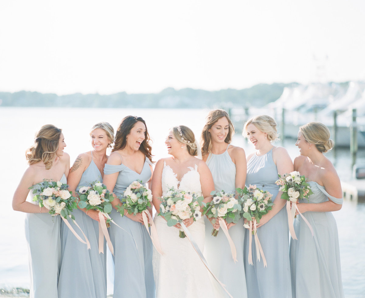 Bride and bridesmaids laugh on dock