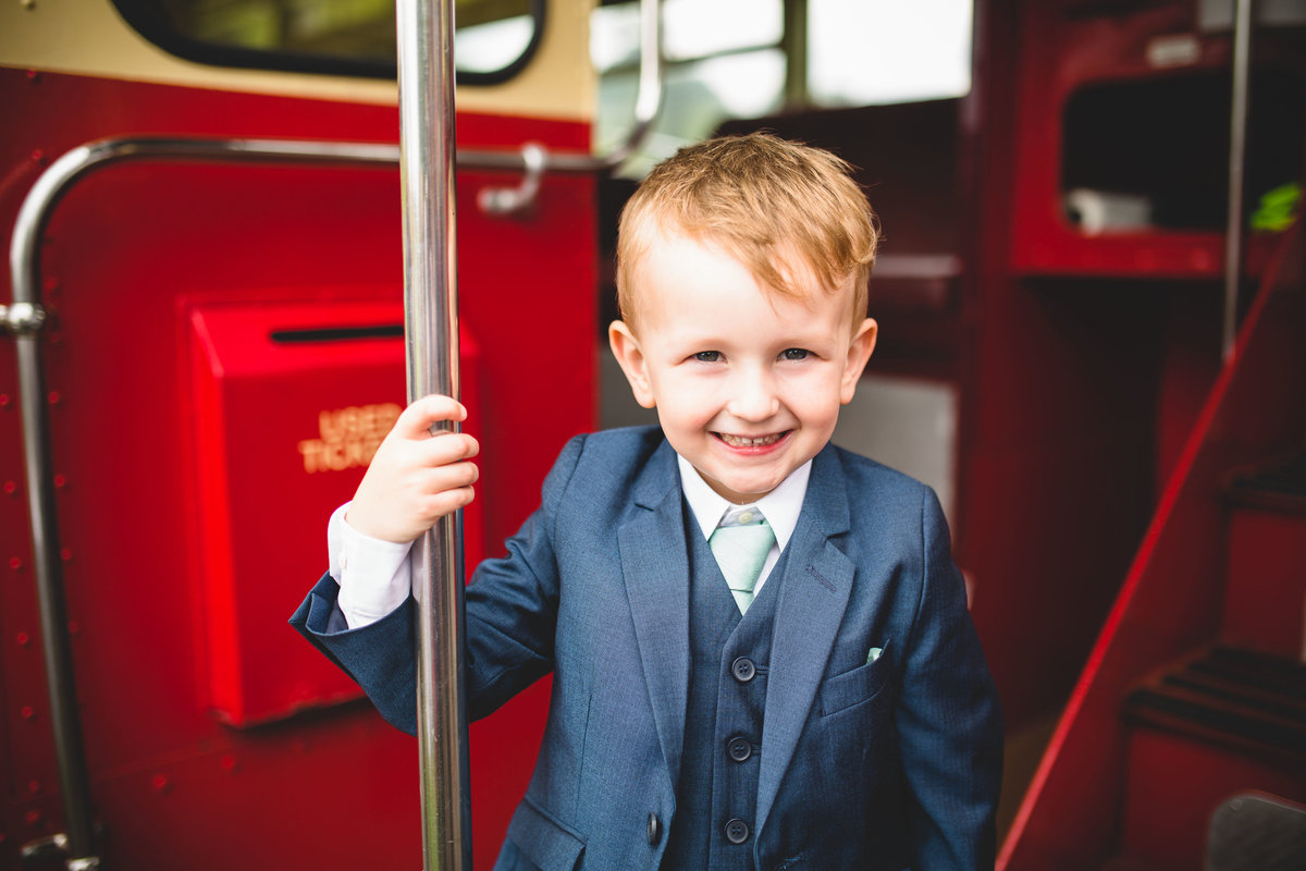 a page boy on the vintage red wedding bus