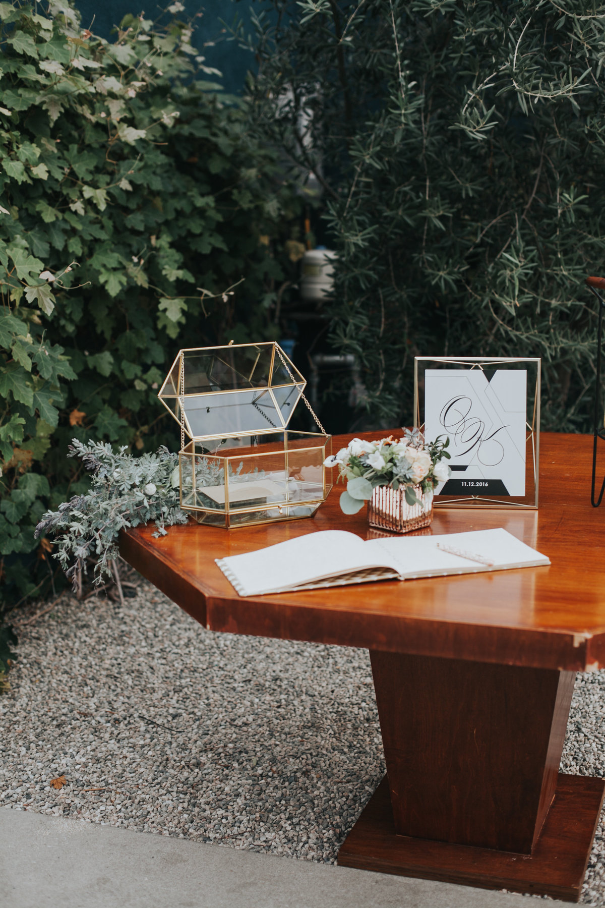 Modern wedding welcome table with glass geometric cardbox and eucalyptus leaves