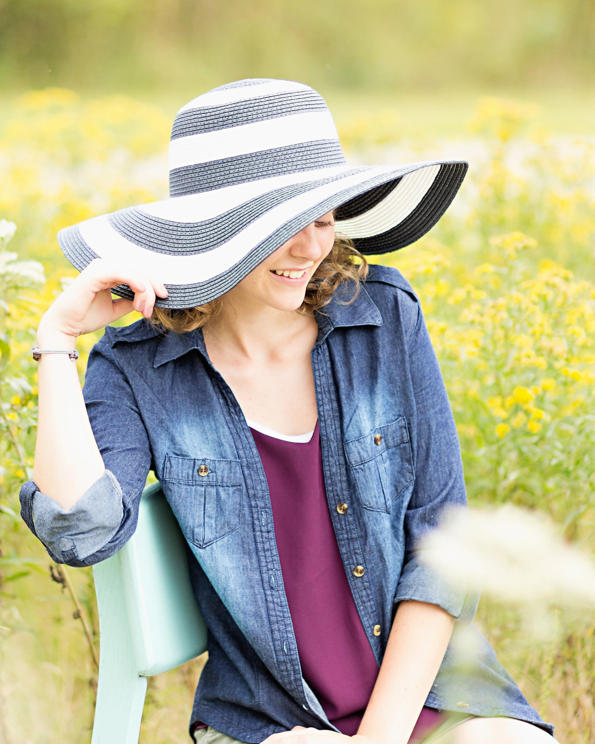 Senior girl sitting in field of wild flowers wearing large hat