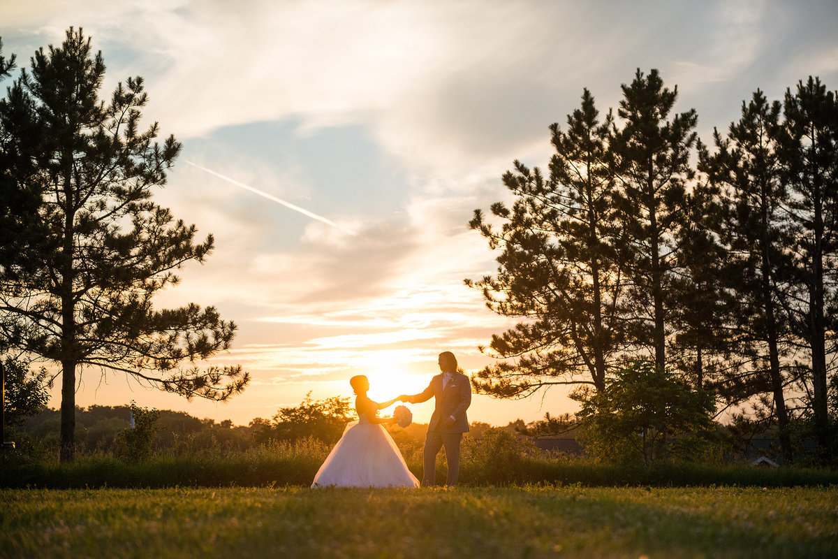 Bride and groom dancing in field at sunset