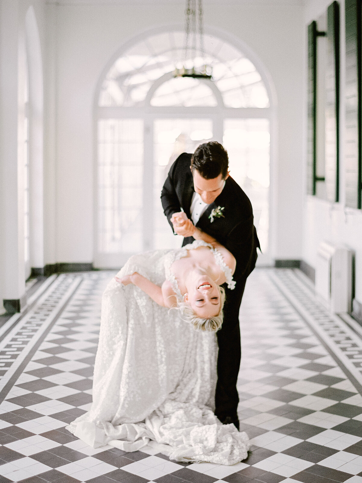 groom dipping bride on black and white tile floor at Lowndes Grove patio Wedding reception
