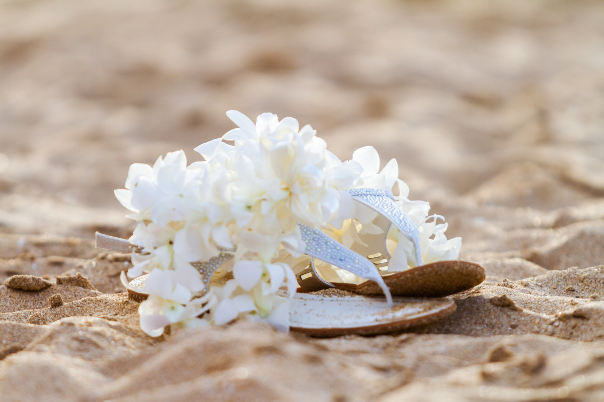 Brides sandals and flower lei in the sand during Kauai wedding.