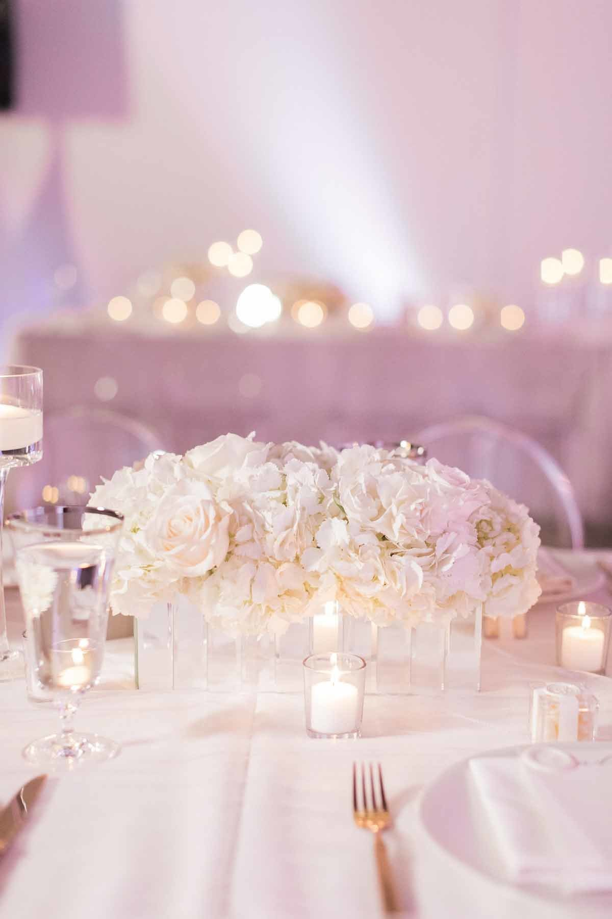 White hydrangea and rose arrangement lit by hundreds of candles is so romantic for a reception look.