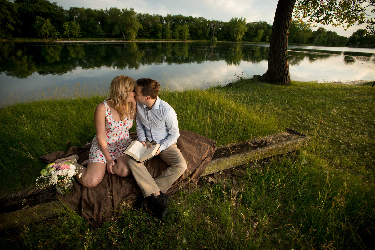 A couple kiss on the outdoor lake front alter that will be the site of their wedding