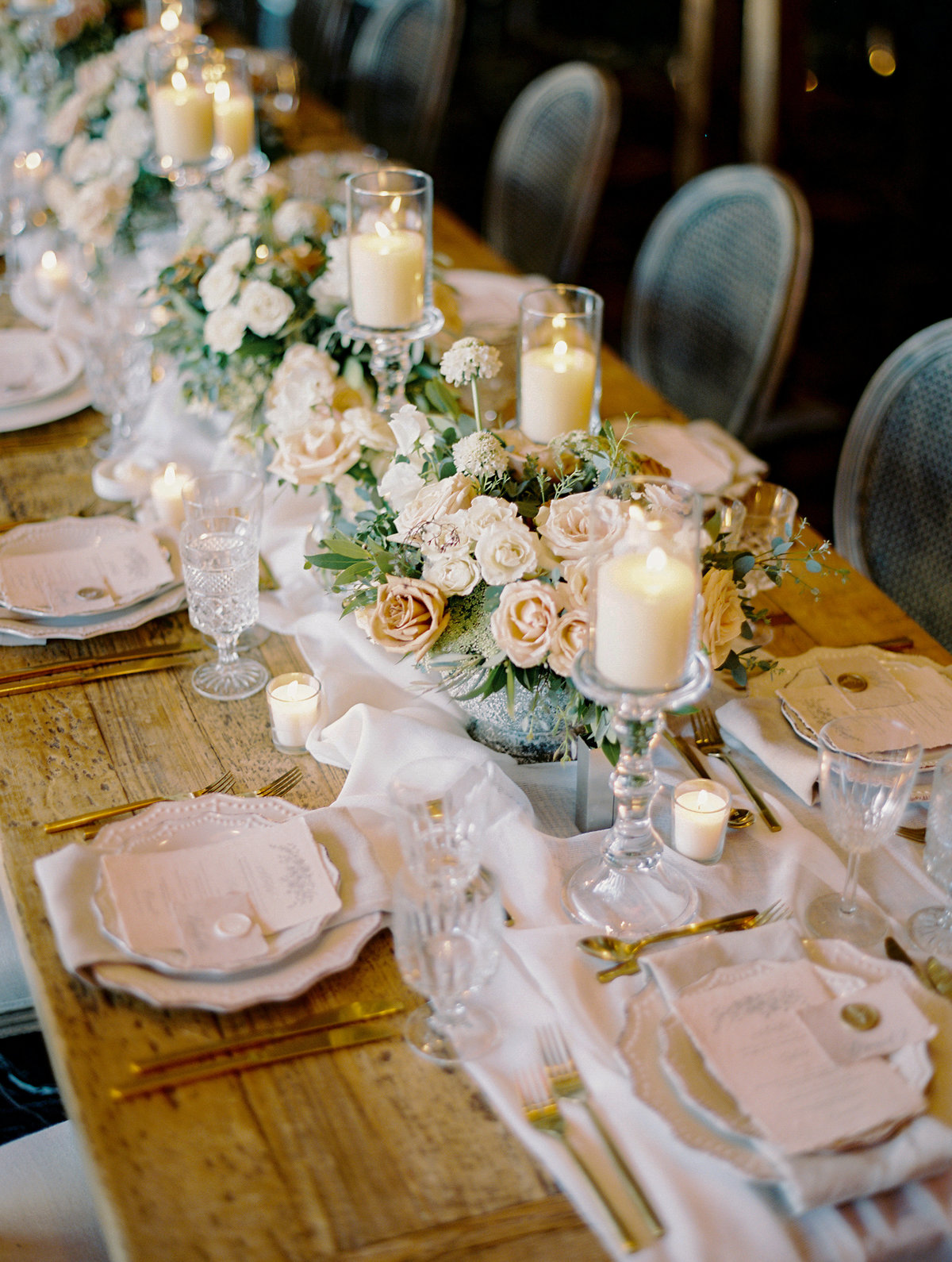 a rustic wood table with white flowy linen and a floral centerpiece with white, ivory and rust colored roses with white candles