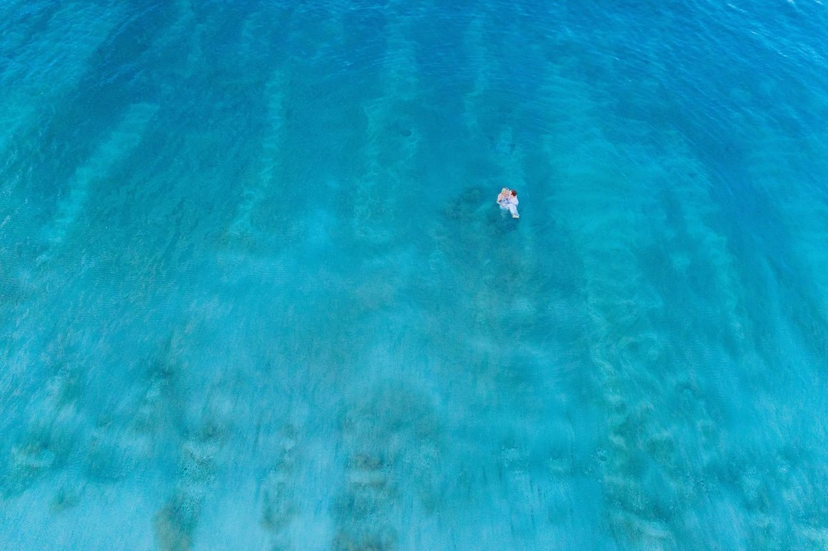 Couple holding each other in the ocean, photographed by drone