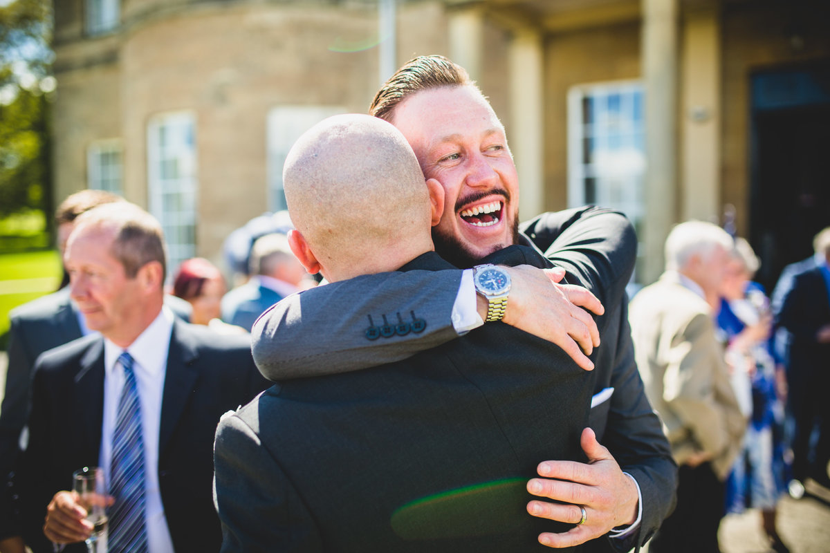 the groom hugging a friend after the wedding ceremony