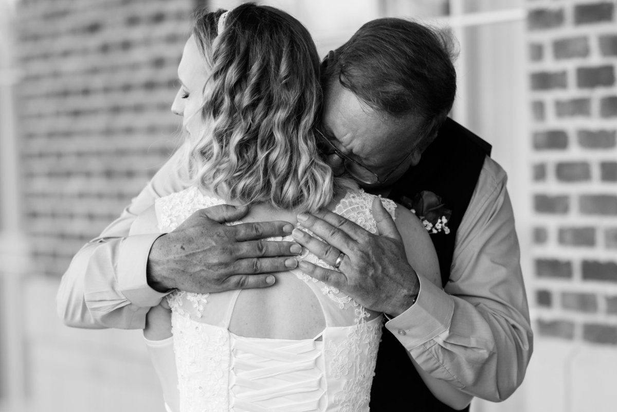 dad hugging daughter on wedding day at hilton garden inn by suffolk virginia wedding photographer