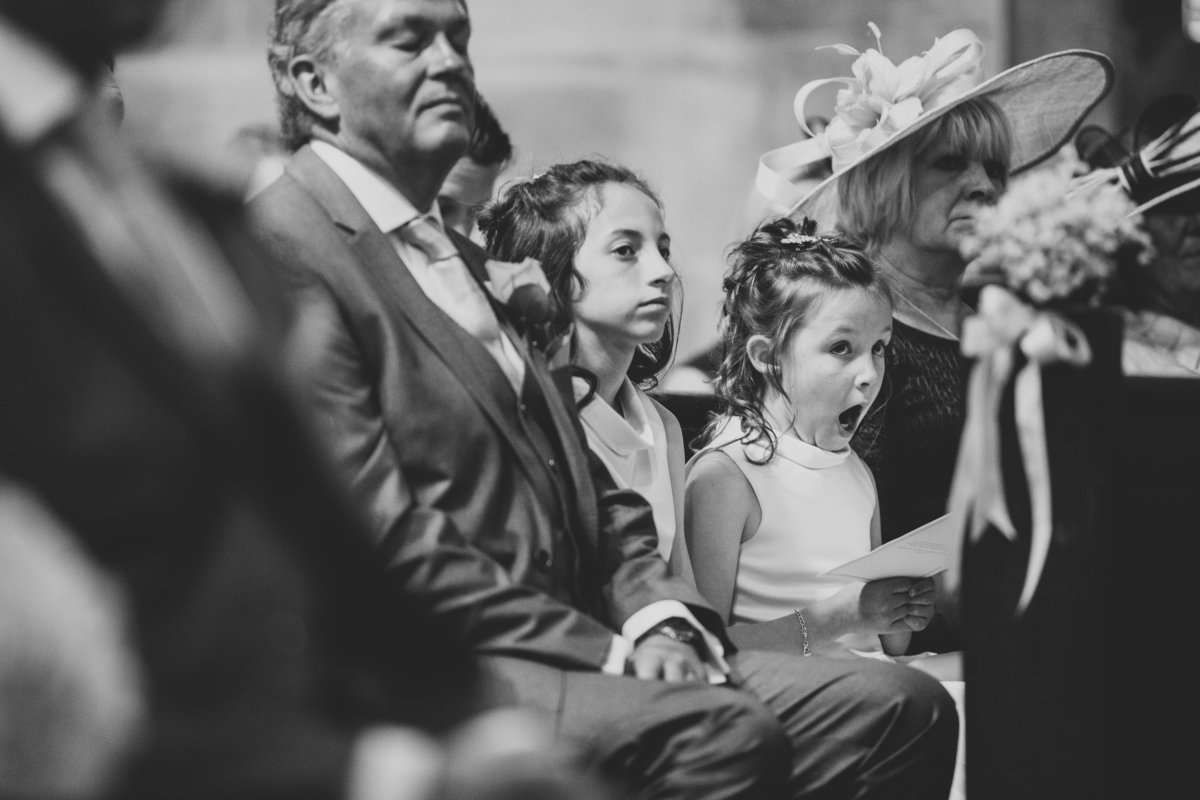 bridesmaid yawning in church and father with eyes closed