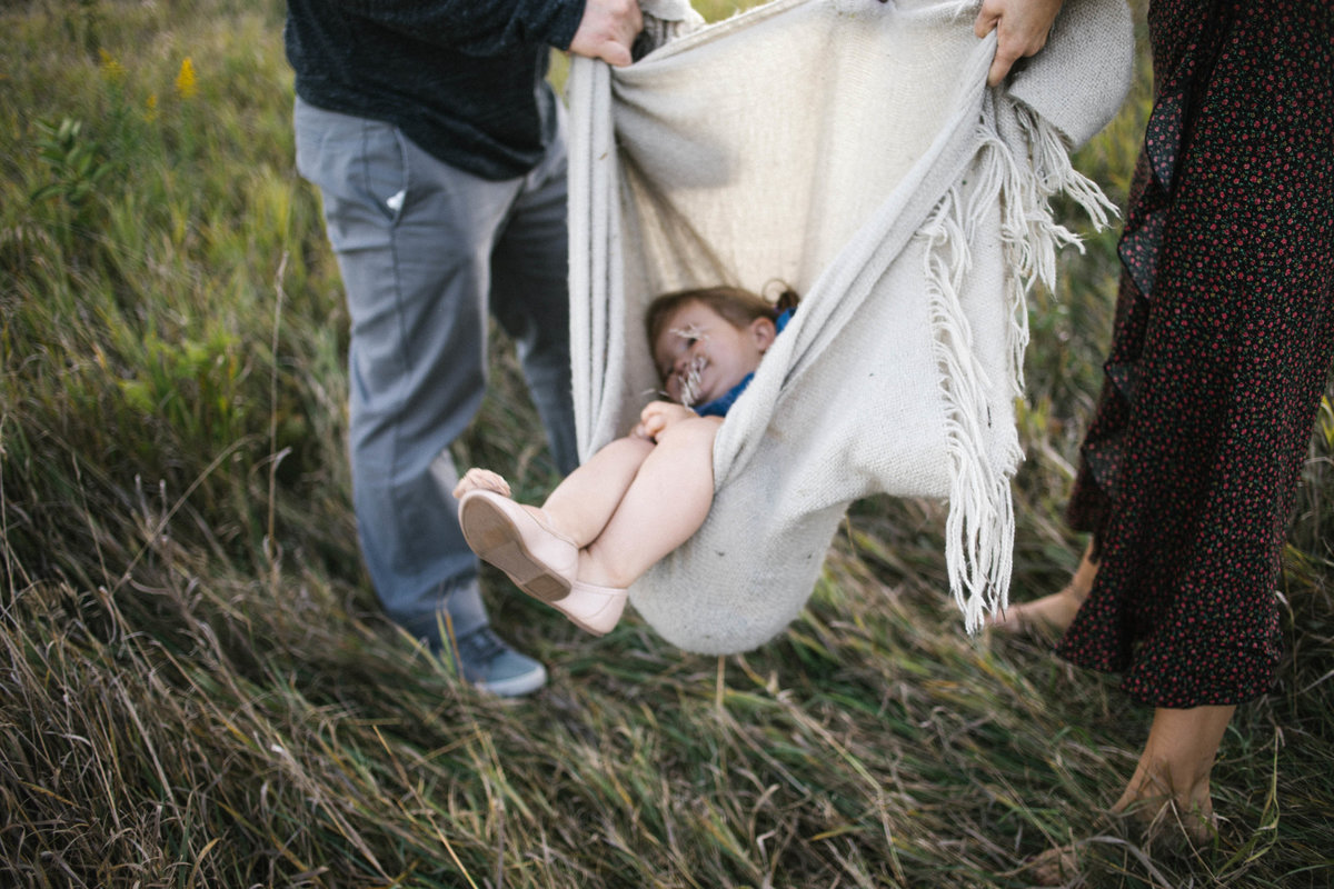 Little girl laying in a blanket swing with her parents