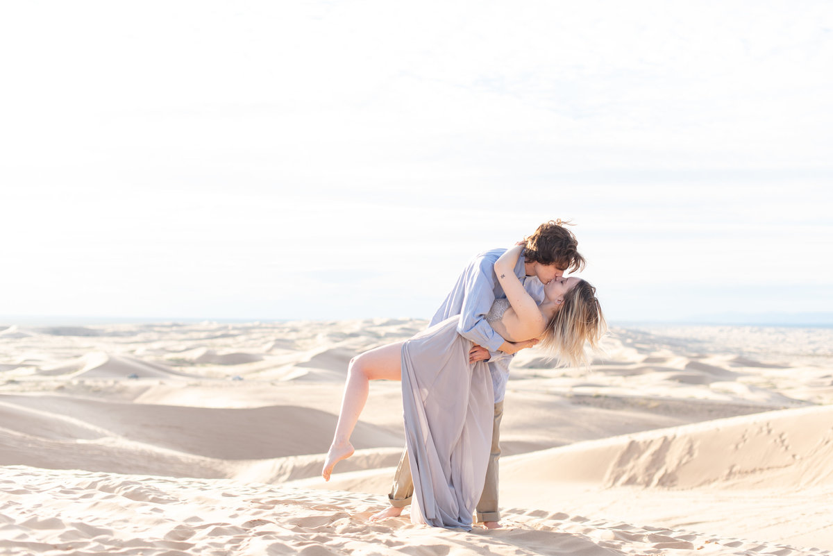 boy dips girl and kisses her at glamis sand dunes
