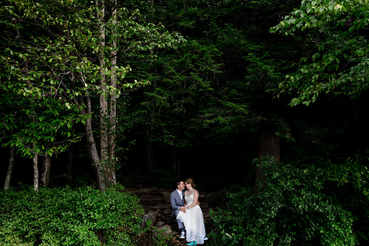 Dublin New Hampshire wedding the couple sits among the lush trees that look out at Mount Monadnock and laugh