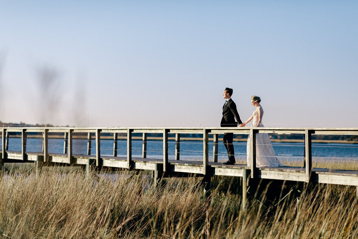 Bride and groom walking down wooden dock on river at Charleston Wedding
