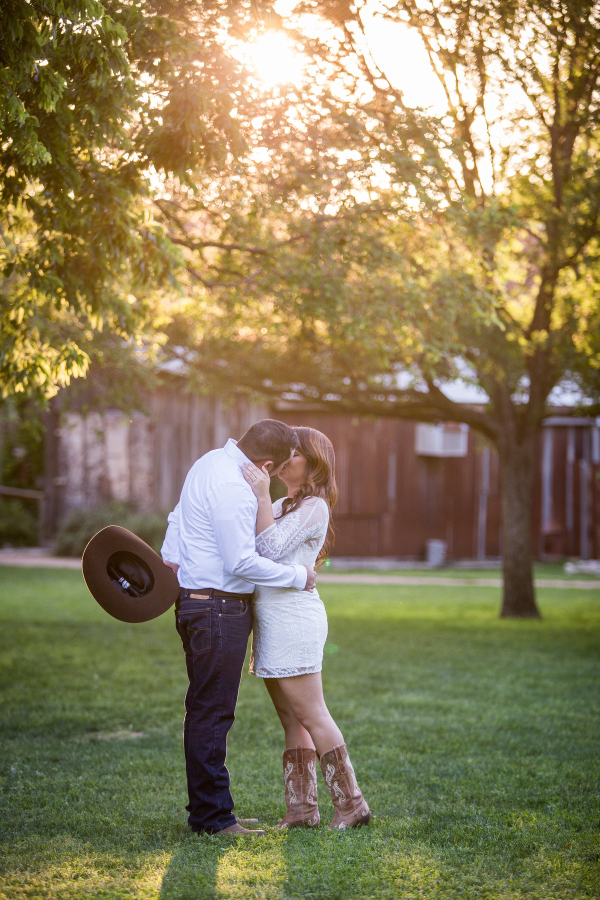 Engaged couple kissing in Gruene, Texas. Man is holding cowboy hat behind his back and sun is shining through trees.