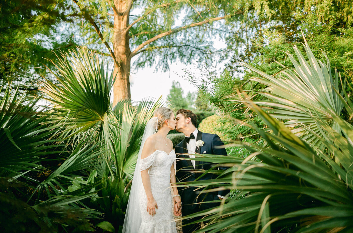 Bride in white wedding dress and veil and Groom in blue tuxedo kissing in green palm leaves