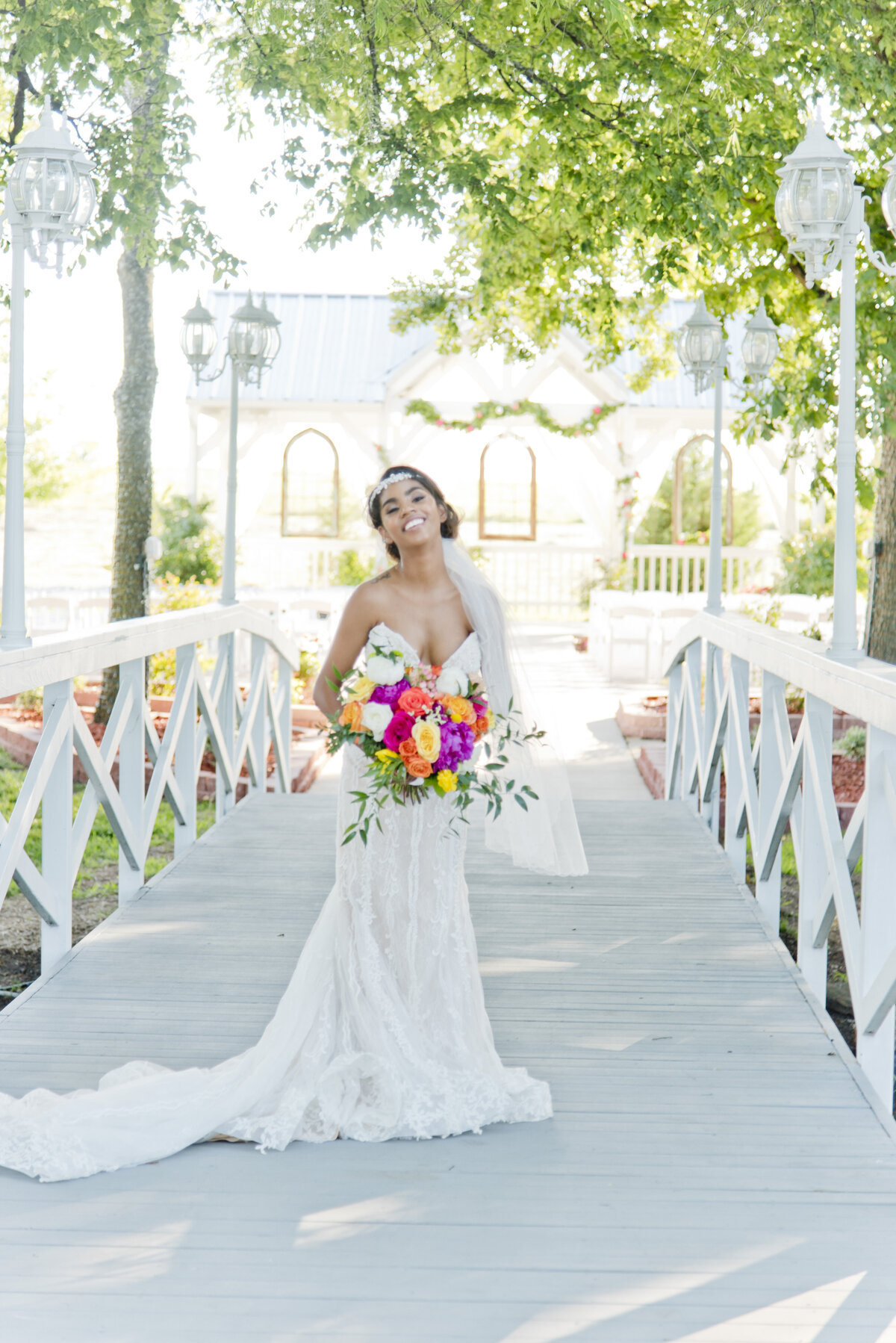 Bride standing on beautiful bridge with colorful bouquet in Fort Worth