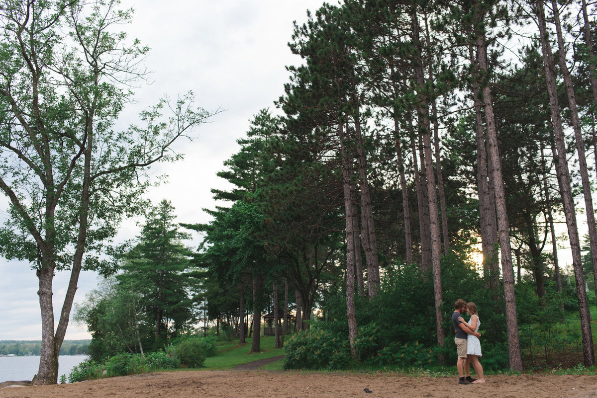 couple standing together among tall pine trees at sunset
