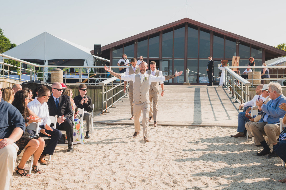 photo of grooms walking down the aisle during wedding ceremony on the beach at Pavilion at Sunken Meadow