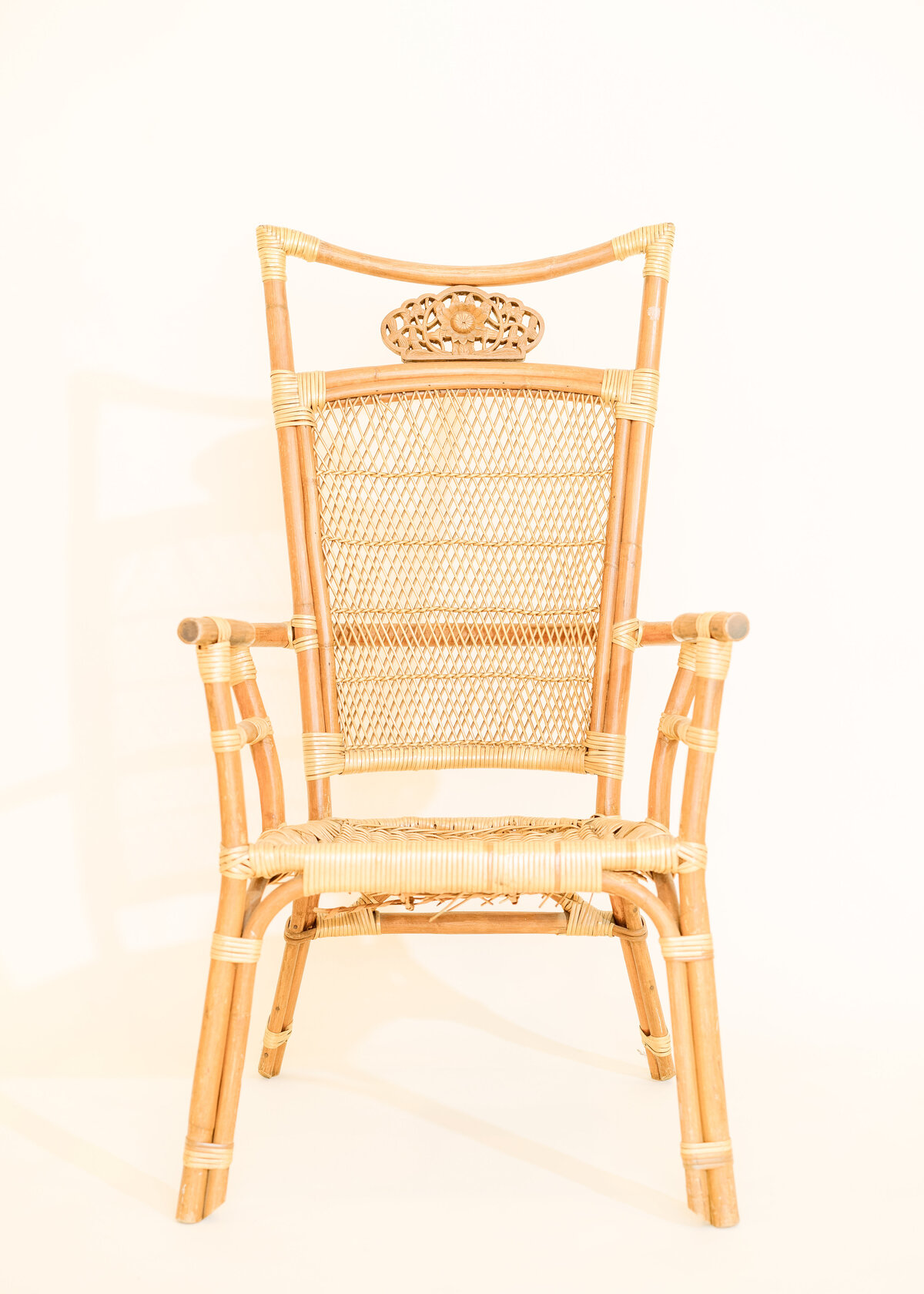 An ornate luxury rattan chair is photographed against a white wall.
