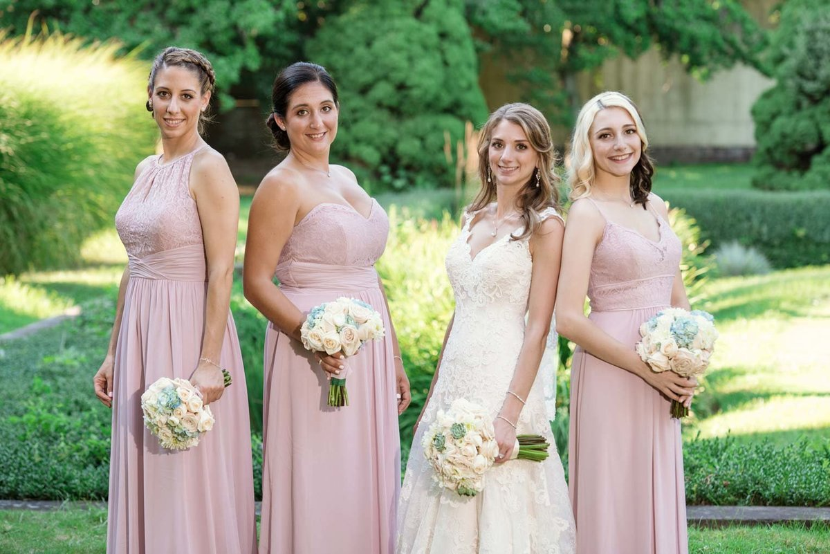 The bridesmaids wearing pink dresses at The Mansion at Oyster Bay