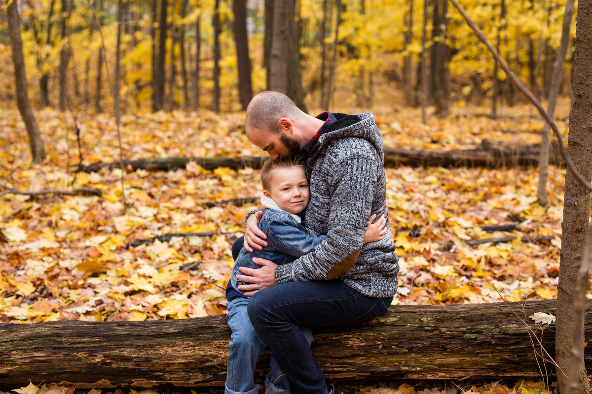 Father and son sitting on log in forest {Oakville Family Photographer}