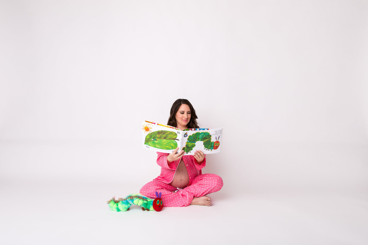 Hungry Caterpillar themed maternity photography session in studio on white backdrop in San Antonio.